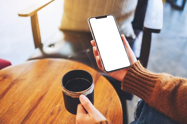 Modellbild einer frau mit schwarzem handy mit leerem bildschirm und kaffeetasse