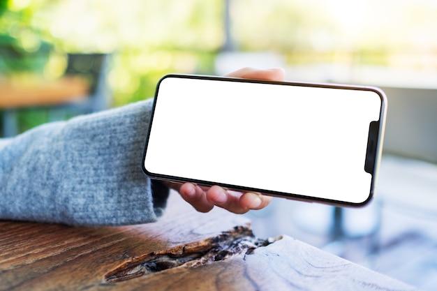 Modellbild einer hand, die ein schwarzes mobiltelefon mit leerem desktop-bildschirm hält und zeigt
