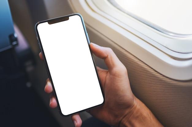 Modellbild einer hand, die ein schwarzes mobiltelefon mit leerem desktop-bildschirm neben einem flugzeugfenster hält