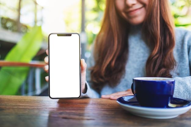 Modellbild einer schönen frau, die ein schwarzes handy mit leerem bildschirm im café hält und zeigt
