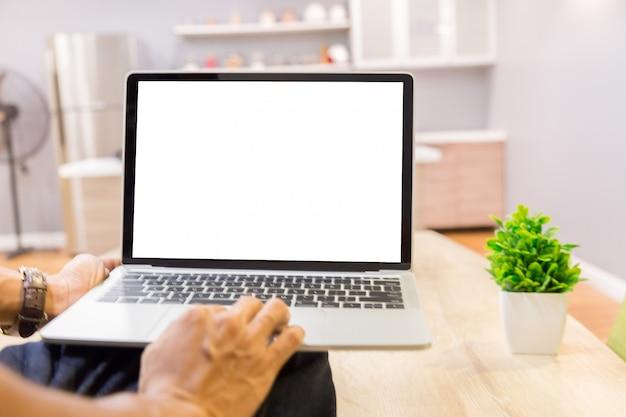Modellbild eines geschäftsmannes unter verwendung des laptops mit dem leeren weißen tischplattenschirm, der im haus arbeitet
