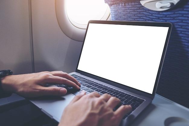 Modellbild eines mannes, der einen laptop mit leerem weißen desktop-bildschirm verwendet und tippt, während er in der kabine sitzt