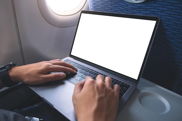 Modellbild eines mannes, der laptop-computer mit leerem weißen desktop-bildschirm beim sitzen in der kabine verwendet und tippt