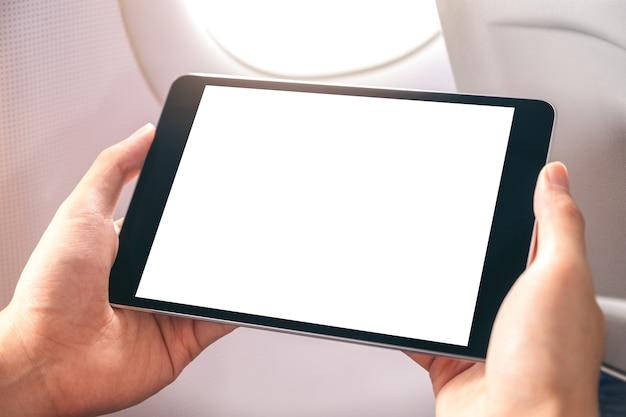 Modellbild eines mannes, der schwarzen tablett-pc mit leerem weißen desktop-bildschirm neben einem flugzeugfenster hält und betrachtet