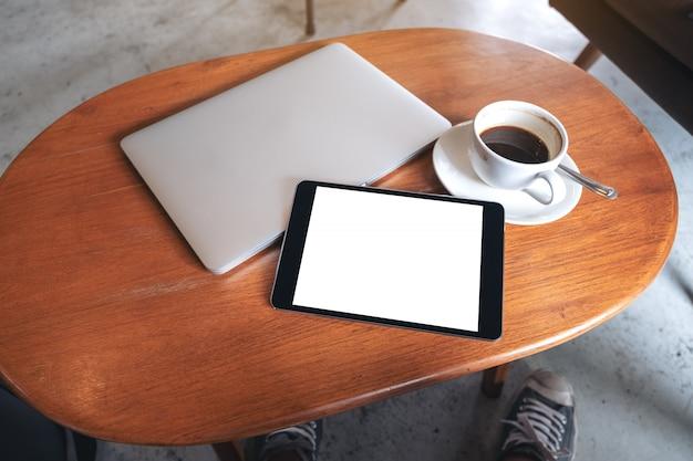 Modellbild eines schwarzen tablet-pcs mit leerem weißen desktop-bildschirm mit laptop und kaffeetasse auf holztisch