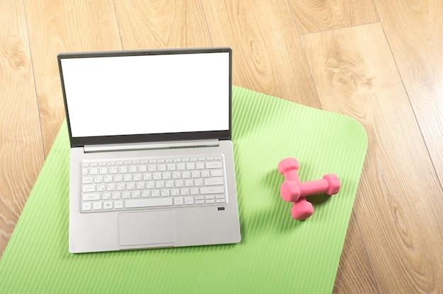 Modellbild sport online-workouts zu hause fitnessstudio mit computer oder telefon und sportlichem zubehör