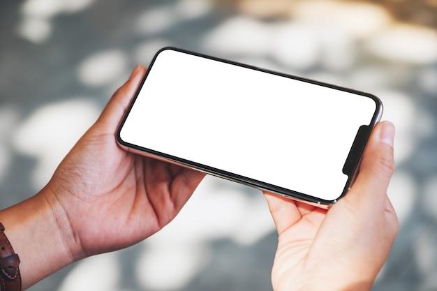 Modellbild von händen, die ein schwarzes mobiltelefon mit leerem desktop-bildschirm halten
