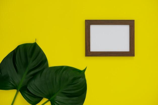 Modellbilderrahmen mit platz für text oder bild auf gelbem hintergrund und tropischem blatt.