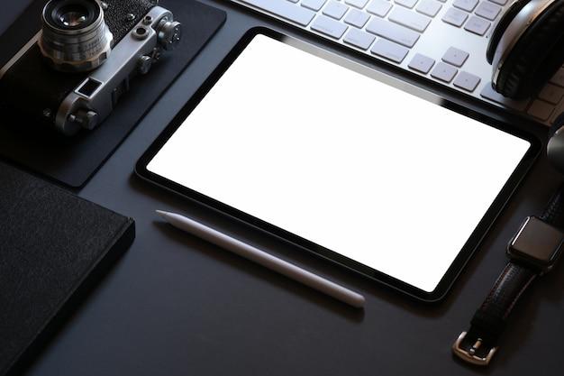 Modellbüro stationär mit tablette des leeren bildschirms auf dunklem ledernem arbeitsplatzschreibtisch