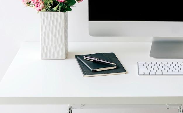 Modellcomputer mit tastatur, vase der blume und buch auf weißer tabelle.