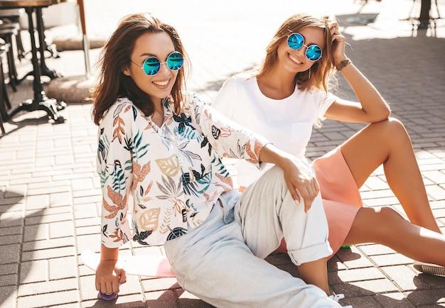 Modelle im sonnigen sommertag in der hipster-kleidung, die auf penny skateboard auf der straße sitzt