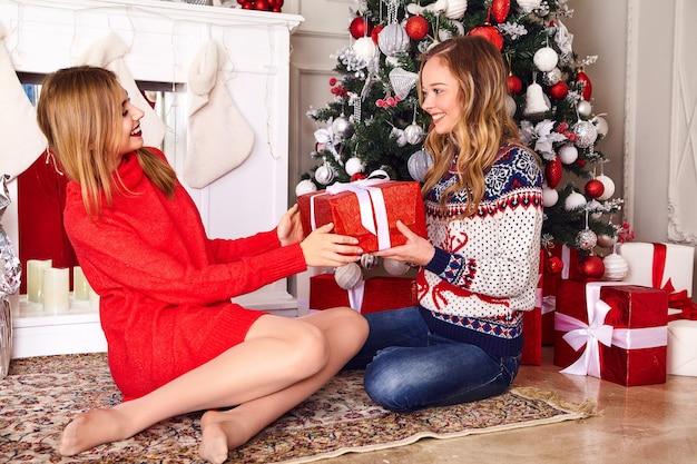 Modelle in warmen winterpullovern sitzen nahe geschmücktem weihnachtsbaum am silvesterabend.