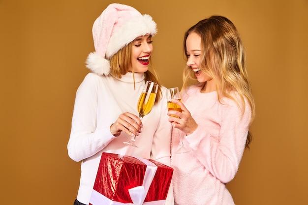 Modelle mit großer geschenkbox, die champagner in gläsern trinken, die neujahr feiern