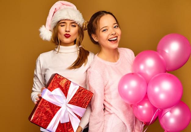 Modelle mit großer geschenkbox und rosa luftballons an weihnachten