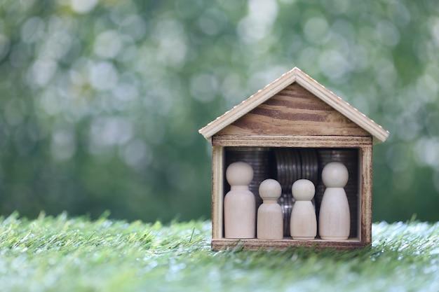 Modellfamilie im modellhaus und stapel münzgeld auf natürlichem grünem hintergrund, sparen sie geld für die vorbereitung in zukunft und familienfinanzierungskonzept
