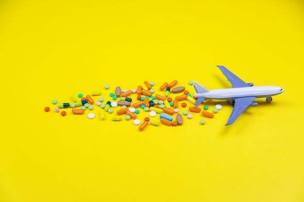 Modellflugzeug mit bunten pillen aus reisekrankheit nahaufnahme auf gelbem grund. konzept krankheit in reisen.selektiver fokus
