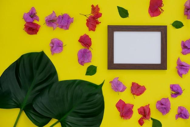 Modellfotorahmen mit platz für text oder bild auf gelbem hintergrund und tropischem blatt und blume.