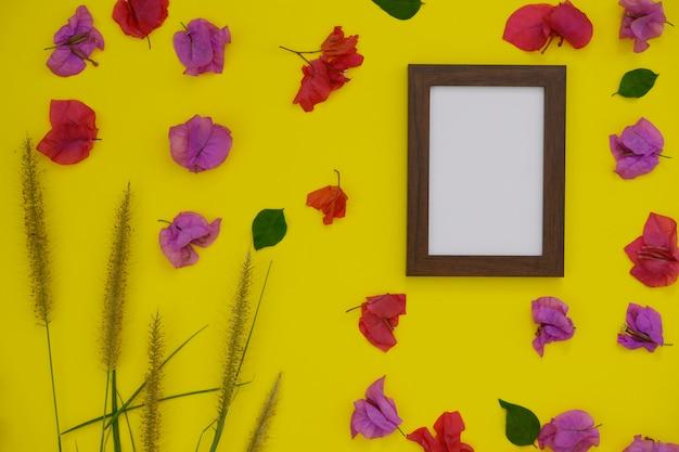 Modellfotorahmen mit platz für text oder bild auf gelbem hintergrund und tropischen blumen.