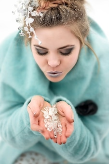 Modellfrau gekleidet in mantel und magisches make-up, das blütenblätter im verschneiten wald bläst