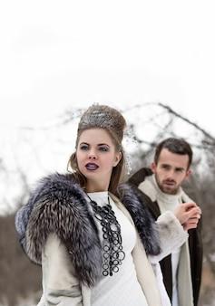 Modellfrau gekleidet in mantel und magisches make-up im wald, der einen mann hält, ist hand