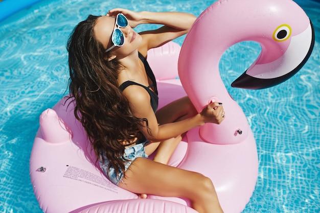 Modellfrau mit perfektem körper im schwarzen bikini und in der sonnenbrille, die auf einem aufblasbaren rosa flamingo im schwimmbad im freien aufwirft