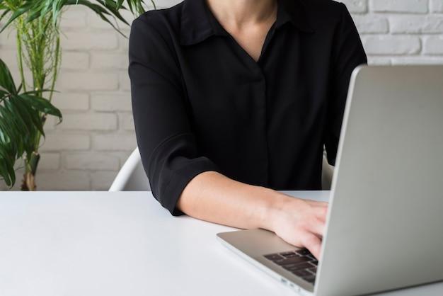 Modellgeschäftsfrau, die an laptop arbeitet
