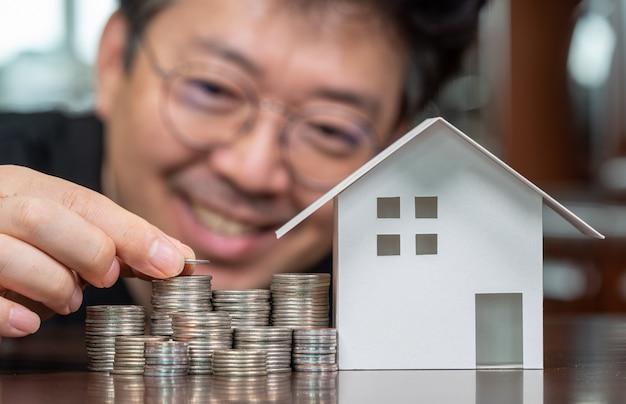 Modellhäuser und gestapelte münzen. eigenheimkredite. hypotheken und kredite.