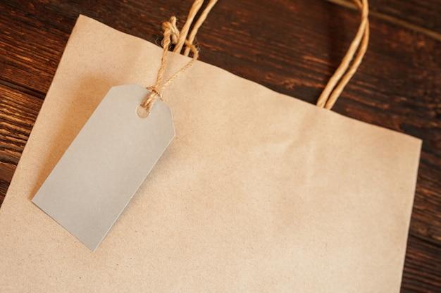 Modellhandwerkspapiereinkaufstasche mit tag auf weinleseholztisch