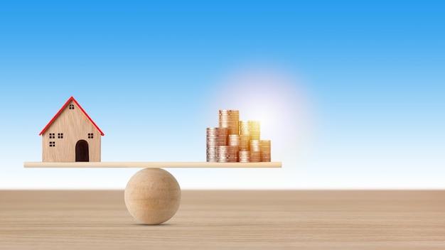 Modellhaus auf wippe balancieren mit stapelmünzen geld auf blauem hintergrund.