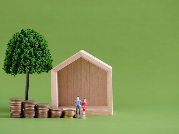 Modellhaus mit miniaturmenschen und münzen auf grünem hintergrund. platz für text