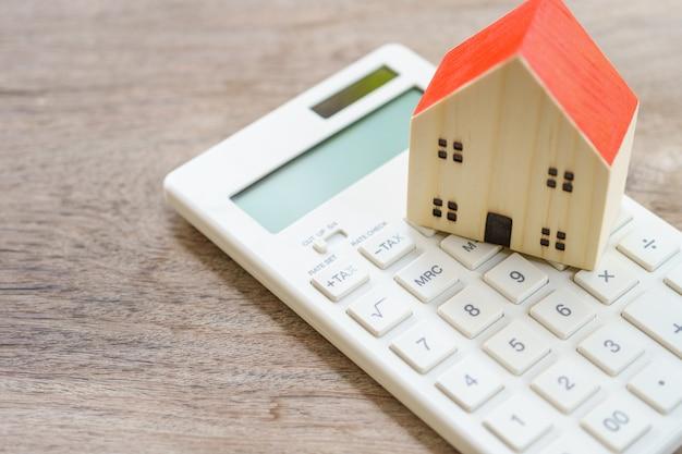 Modellhaus modell wird auf einen taschenrechner gelegt. hintergrundimmobilien-immobilienkonzept