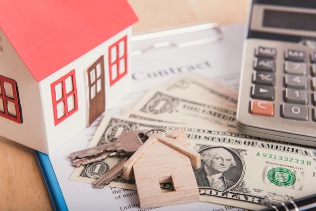 Modellhaus- und -dollargeld mit vertragspapier auf tabelle. darlehen zu hause finanzieren konzept.