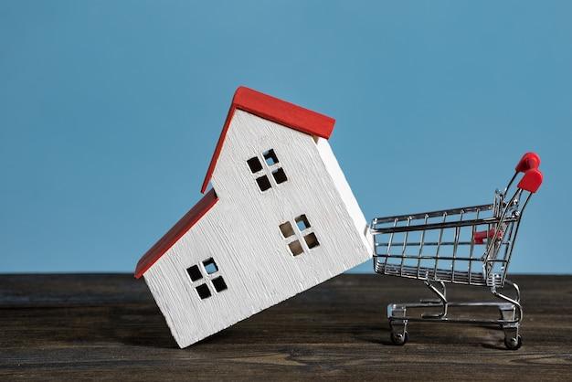 Modellhaus und einkaufswagen an einer blauen wand. kauf nach hause, hypothekenkonzept