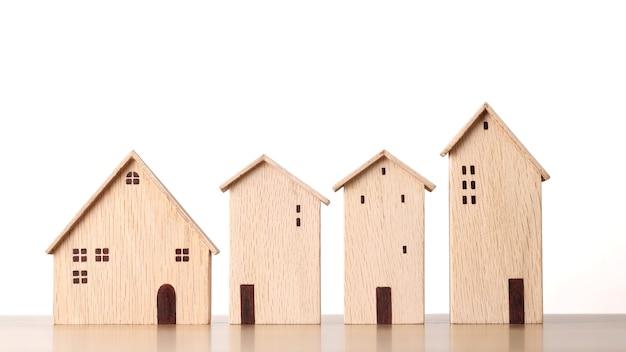 Modellholzhäuser auf hölzernem schreibtisch auf weißem hintergrundstudio