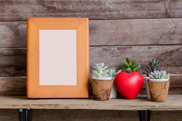 Modellieren sie holzrahmen auf regal mit rustikalem hölzernem hintergrund des valentinsgrußherzens und -kaktus
