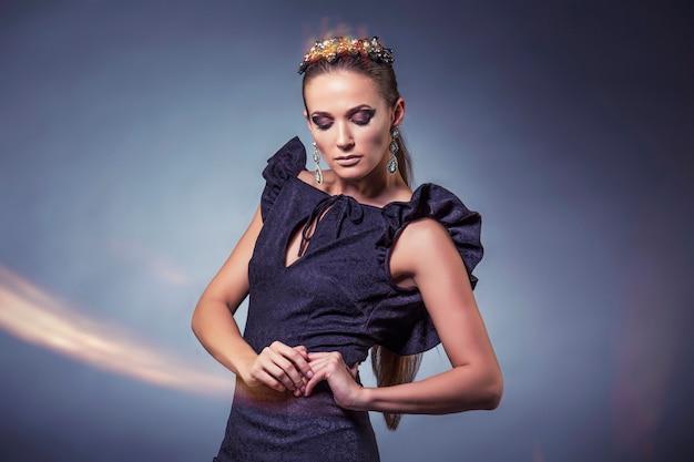 Modellieren sie schöne frauen in modischen kleidern und accessoires, die isoliert auf einem schwarzen hintergrund im studio geschossen werden