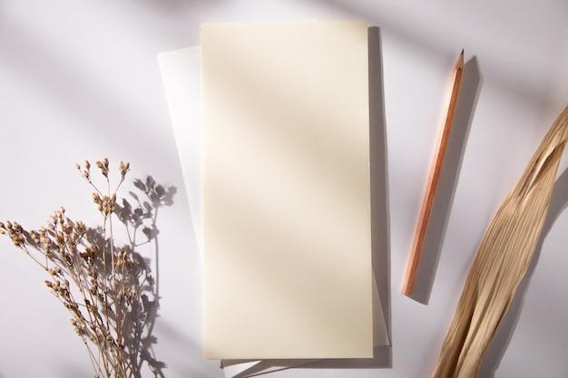 Modellkarten mit blume und bleistift auf tisch