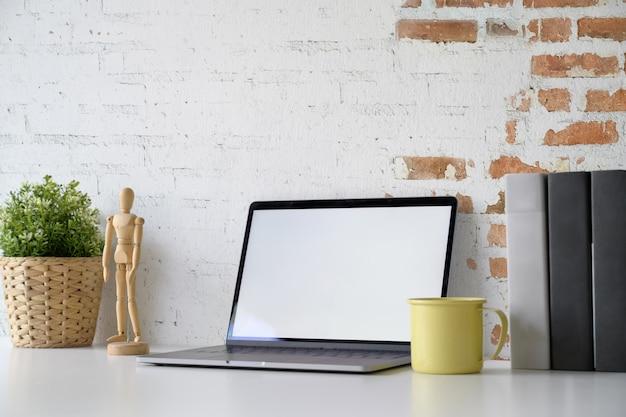 Modelllaptop, der leeren bildschirm auf weißem schreibtischarbeitsplatz zeigt.