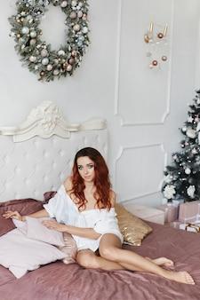 Modellmädchen im herrenhemd auf nacktem körper, der auf dem bett in für weihnachtseinrichtung verziert aufwirft