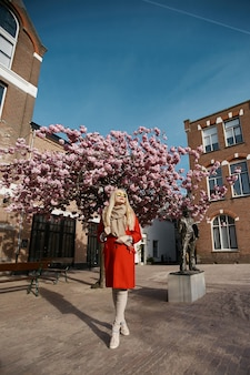 Modellmädchen im roten mantel, der unter rosa blühendem baum am städtischen hintergrund steht.