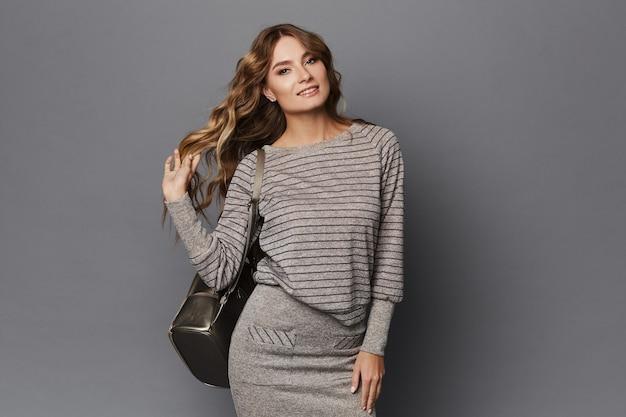 Modellmädchen in einem rock und einem grauen pullover mit einem rucksack, der auf einem grauen hintergrund aufwirft, lokalisiert