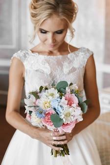 Modellmädchen mit hochzeitsfrisur und rechtem make-up im weißen spitzenkleid mit dem großen luxusstrauß der exotischen blumen in ihren händen, die am innenraum aufwerfen