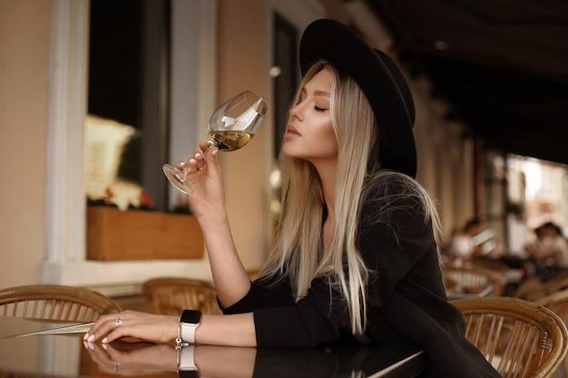 Modellmädchen mit sanftem make-up und blondem haar, das am sommerabend wein am kaffeetisch genießt.