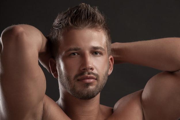 Modellmann mit einer offenen brust auf einem dunklen hintergrund, muskulöser körper eines jungen mannes in jeans. in einem studio gedreht.