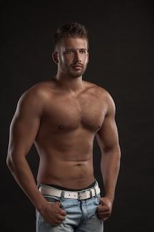 Modellmann mit einer offenen brust auf einem dunklen hintergrund, muskulöser körper eines jungen mannes in jeans