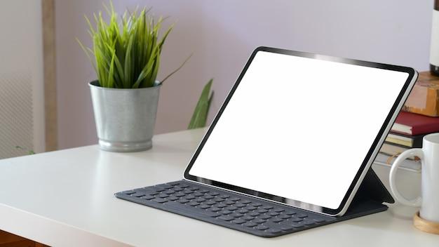Modelltablet-computer und leerer bildschirm auf arbeitsplatz