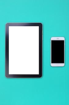Modelltablette und smartphone auf grünem pastellhintergrund