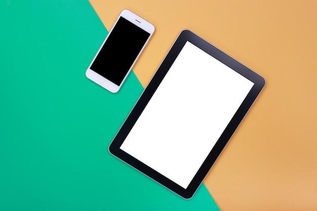 Modelltablette und smartphone auf grünem und orange pastellhintergrund