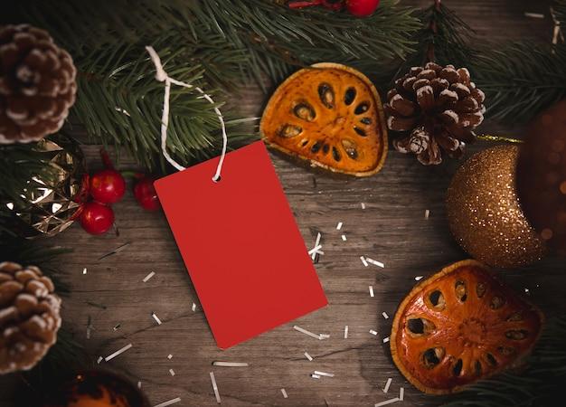 Modelltag-papierkarte mit kiefernkegel-weihnachtsdekoration auf hölzernem tabellenhintergrund.