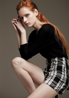 Modelltest mit dem jungen schönen mode-modell, das das schwarze hemd und rock sitzen auf stuhl auf grauem hintergrund trägt